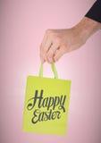 Passi la tenuta della borsa verde con con tipo contro fondo rosa immagini stock libere da diritti