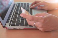 Passi la tenuta della carta di credito e digitare i dati in un computer portatile del computer fotografia stock libera da diritti