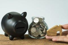 Passi la tenuta della casa miniatura di legno con le monete in barattolo e nel nero fotografia stock