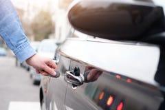 Passi la tenuta della chiave dell'automobile e l'apertura della porta di automobile Fotografia Stock Libera da Diritti