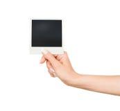 Passi la tenuta della foto istantanea in bianco su fondo bianco Fotografie Stock Libere da Diritti