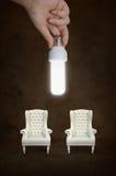 Passi la tenuta della lampadina con la sedia d'annata Immagine Stock Libera da Diritti