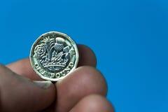 Passi la tenuta della moneta di libbra BRITANNICA nuova su un fondo blu Immagini Stock