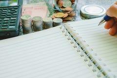 Passi la tenuta della penna per scrivere sul taccuino in bianco con le banconote Fotografia Stock