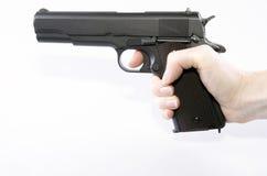 Passi la tenuta della pistola su un fondo bianco Fotografie Stock Libere da Diritti