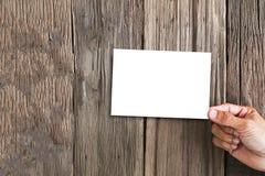 Passi la tenuta della struttura bianca della foto sul fondo di legno di lerciume d'annata Fotografia Stock Libera da Diritti