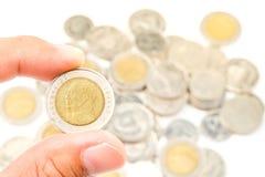 Passi la tenuta della Tailandia dieci monete di baht con il dito Fotografie Stock Libere da Diritti