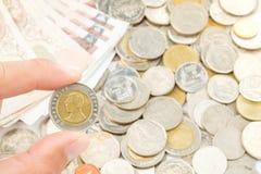 Passi la tenuta della Tailandia dieci monete di baht con il dito Immagini Stock