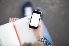Passi la tenuta dello smartphone contro un quaderno con una matita fotografia stock libera da diritti