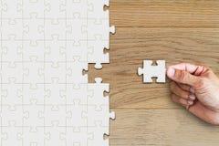Passi la tenuta e l'inserimento del puzzle mancante del pezzo sulla tavola di legno fotografie stock libere da diritti