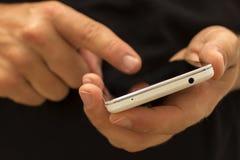 Passi la tenuta e per mezzo di uno smartphone/telefono Immagine Stock Libera da Diritti