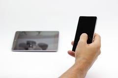 Passi la tenuta e per mezzo di uno smartphone/telefono (isolati) Immagini Stock
