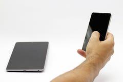 Passi la tenuta e per mezzo di uno smartphone/telefono (isolati) Immagine Stock Libera da Diritti