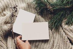 Passi la tenuta le cartoline di Natale o della lista di obiettivi vuote su simpl alla moda Fotografia Stock