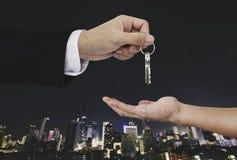Passi le chiavi della tenuta con il fondo della città, il bene immobile ed il concetto della proprietà Immagini Stock Libere da Diritti