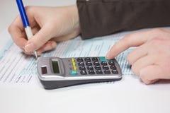 L'imposta sul reddito di riempimento si forma con il calcolatore e la penna fotografie stock libere da diritti