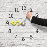 Passi le mani di orologio della tenuta nella forma dei fondi USD, parete di mattoni bianca, Fotografia Stock