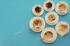 Passi le tazze di caffè della tenuta con latte e senza nella forma dei palloni sul fondo della carta blu modificato Fotografie Stock Libere da Diritti
