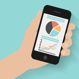 Passi lo Smart Phone della tenuta con i grafici su fondo moderno Fotografia Stock
