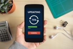 Passi lo Smart Phone della tenuta con il concetto dell'aggiornamento sullo schermo immagine stock libera da diritti