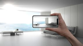 Passi lo Smart Phone della tenuta, l'applicazione dell'AR, simuli la mobilia ed i prodotti di interior design nella casa reale, c immagine stock libera da diritti