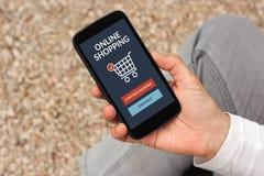 Passi lo smartphone della tenuta con il concetto online di acquisto sullo schermo Immagine Stock Libera da Diritti