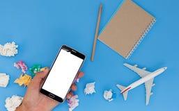 Passi lo smartphone della tenuta con il modello dell'aeroplano e la nota di carta sul blu fotografie stock