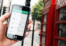 Passi lo smartphone della tenuta con la guida della città a Londra Fotografie Stock