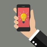Passi lo smartphone della tenuta con la lampadina su esposizione Fotografia Stock