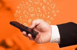 Passi lo smartphone della tenuta con le icone ed i simboli disegnati a mano di media Immagine Stock Libera da Diritti