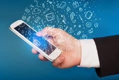 Passi lo smartphone della tenuta con le icone ed i simboli disegnati a mano di media Immagini Stock