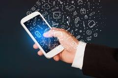 Passi lo smartphone della tenuta con le icone ed i simboli disegnati a mano di media Fotografia Stock