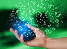 Passi lo smartphone della tenuta con le icone ed i simboli disegnati a mano di media Fotografie Stock