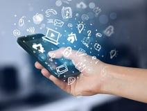 Passi lo smartphone della tenuta con le icone ed il simbolo di media Immagine Stock