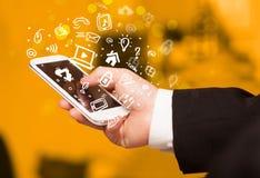 Passi lo smartphone della tenuta con le icone ed il simbolo di media Fotografia Stock Libera da Diritti