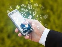 Passi lo smartphone della tenuta con le icone ed il simbolo di media Immagini Stock
