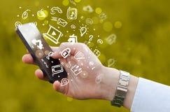 Passi lo smartphone della tenuta con le icone ed il simbolo di media Immagini Stock Libere da Diritti