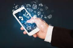 Passi lo smartphone della tenuta con le icone ed il simbolo di media Fotografie Stock