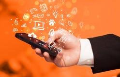 Passi lo smartphone della tenuta con le icone ed il simbolo di media Fotografia Stock