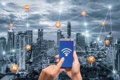 Passi lo smartphone della tenuta con lo scape della città di Bangkok e la rete di wifi Immagini Stock