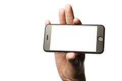 Passi lo smartphone della tenuta, schermo in bianco su fondo bianco Immagini Stock Libere da Diritti