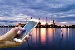 Passi lo smartphone della tenuta sulla pianta vaga a dell'industria della raffineria di petrolio fotografie stock