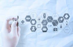 Passi lo stetoscopio della tenuta che mostra il concetto medico su carta sgualcita Fotografie Stock Libere da Diritti