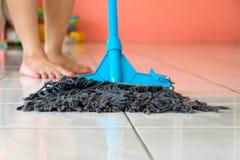 Passi lo straccio sul pavimento di pulito la casa immagini stock