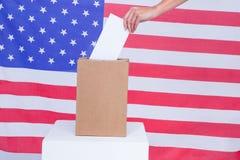 Passi mettere il voto in scatola di voto dietro la bandiera americana Immagini Stock Libere da Diritti