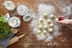 Passi a pasta srotolante i piccoli pezzi di pasta sull'area di lavoro di legno della cucina Fotografia Stock