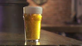Passi a posti un vetro pieno della birra dell'artigiano giù stock footage