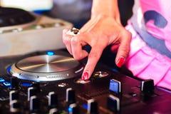 Passi a ragazze il regolatore di musica del DJ per musica mescolantesi in club Immagini Stock Libere da Diritti