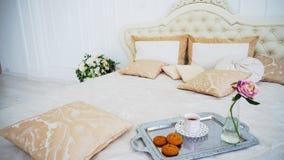 Passi in rassegna il grande letto con i cuscini e le pareti luminose di bianco della camera da letto fotografie stock libere da diritti