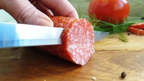 Passi a taglio la salsiccia con salame su un di legno, pomodoro video d archivio